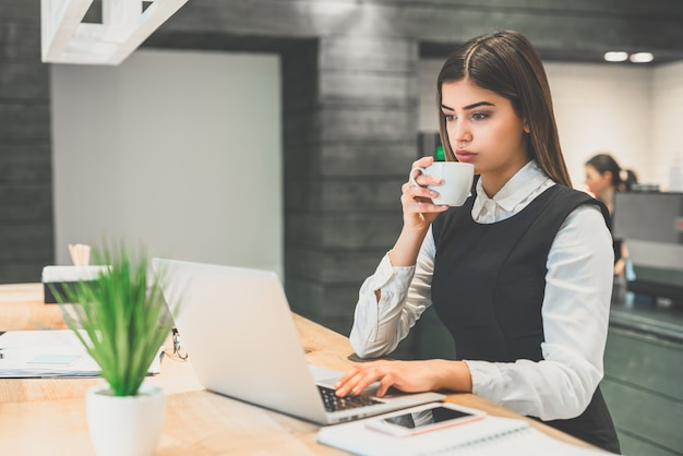 De zakenvrouw die koffie drinkt en met een laptop werkt