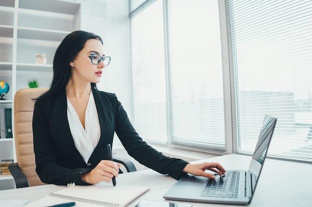 De zakenvrouw die met een laptop aan de balie werkt