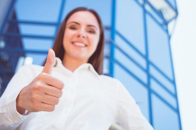 De zakenvrouw duimen omhoog op de achtergrond van het moderne gebouw
