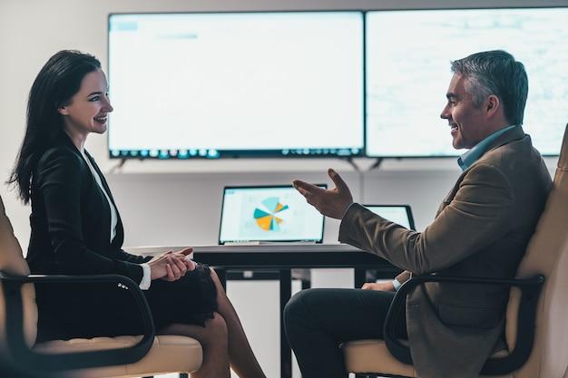 De zakenvrouw en een man bespreken aan tafel in een modern kantoor
