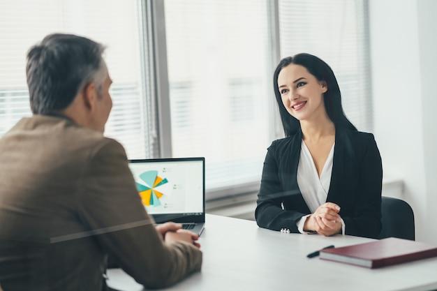 De zakenvrouw en een man praten aan de kantoortafel