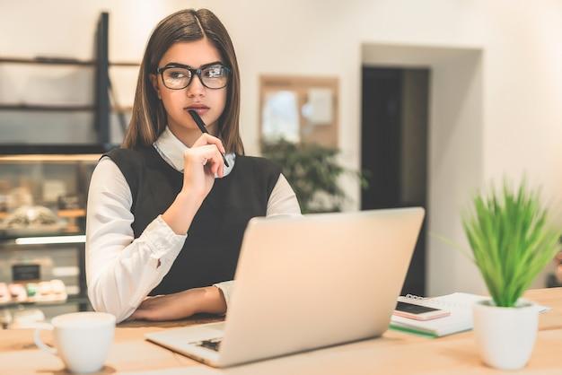 De zakenvrouw met een bril die met een laptop werkt