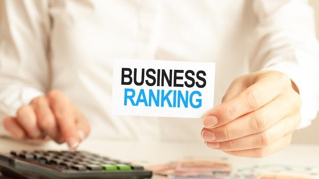 De zakenvrouw toont een kaart met de tekst business ranking en drukt op de rekenmachinetoets. bedrijfsconcept.