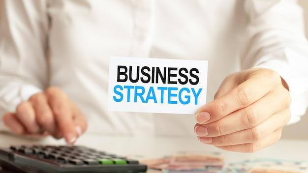 De zakenvrouw toont een kaart met de tekst business strategy en drukt op de rekenmachinetoets
