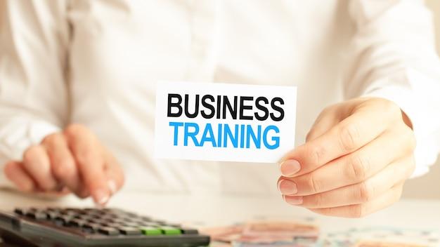 De zakenvrouw toont een kaart met de tekst business training en drukt op de rekenmachinetoets. bedrijfsconcept.
