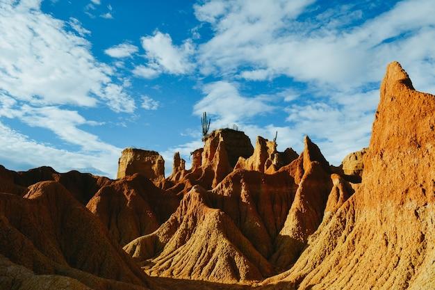 De zanderige rotsen en wilde planten in de tatacoa-woestijn, colombia onder de bewolkte hemel