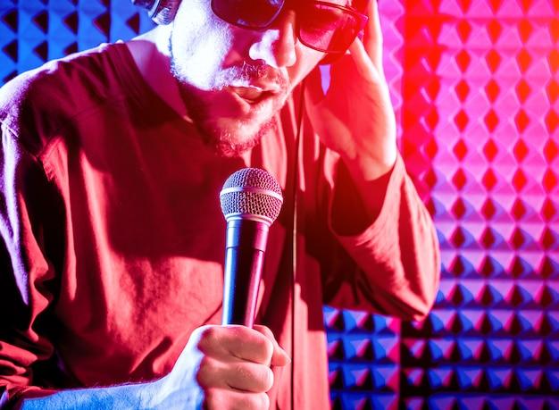 De zanger zingt met een microfoon in de opnamestudio.