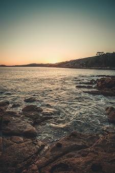 De zee crasht in de rotsen aan de kust tijdens een zonsondergang