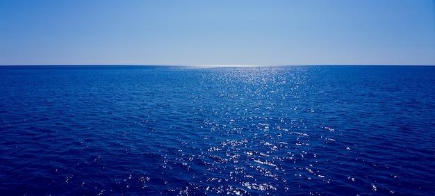 De zee gaat voorbij de horizon met een blauwe lucht op de achtergrond.