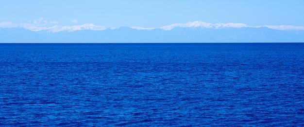 De zee gaat voorbij de horizon met een mistige bergketen op de achtergrond.