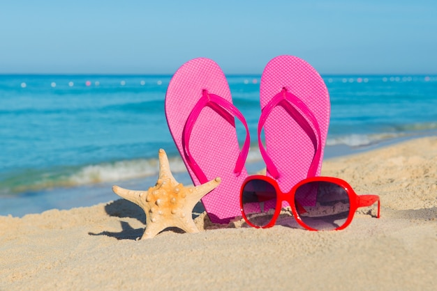 De zee, het strand, het zand en damesaccessoires: roze slippers, rode zonnebrillen en zeesterren