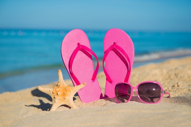 De zee, het strand, het zand en damesaccessoires: roze slippers, zonnebrillen en zeesterren