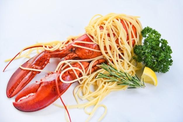 De zeekreeftvoedsel van spaghettizeevruchten op een witte plaat met de citroenrozemarijn van kruidkruiden