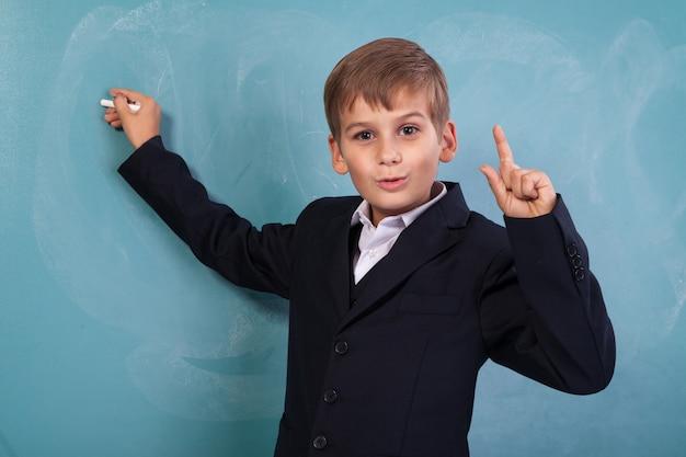 De zeer leuke en positieve student glimlacht en schrijft op schoolbord