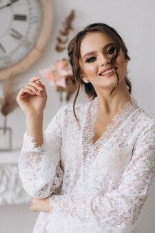 De zeer mooie jonge bruid glimlacht bij de camera