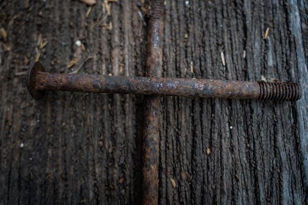 De zeer oude roestige schroeven op de houten vloer