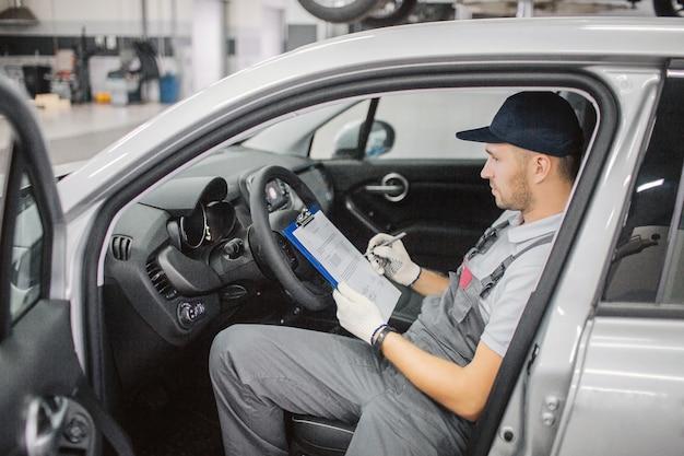 De zekere arbeider zit in auto en ondertekent documenten. hij hield ze op een plastic map. auto is geopend.