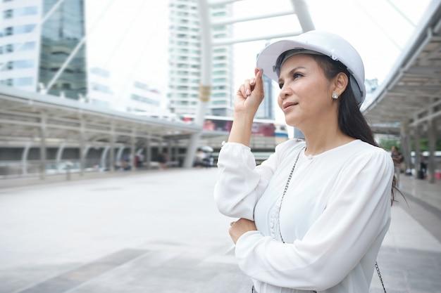 De zekere aziatische werkende vrouw draagt helm, haar hand is gekruiste wapens en wat betreft hoed terwijl in openlucht status.