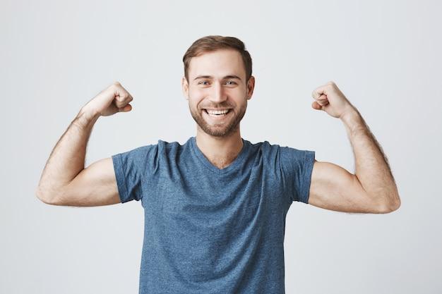 De zekere glimlachende mens opleiding in gymnastiek, buigt sterke bicepsen, toont spieren