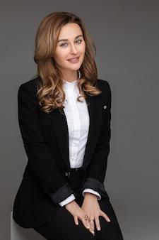 De zekere jonge glimlachende vrouwelijke onderneemster van de bedrijfsleiderondernemer in zwart kostuum op grijze studiomuur.