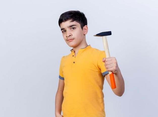 De zekere jonge hamer die van de jongensholding camera bekijkt die op witte achtergrond met exemplaarruimte wordt geïsoleerd