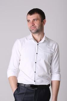 De zekere jonge knappe mens met dient zakken in, die op witte muur worden geïsoleerd