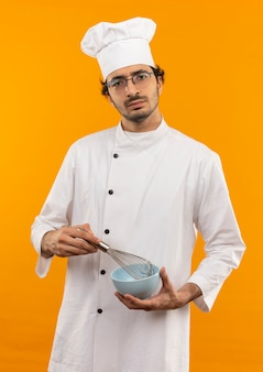 De zekere jonge mannelijke kok die eenvormige chef-kok en de glazenholding dragen zwaait en kom