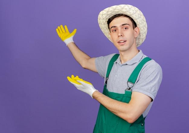 De zekere jonge mannelijke tuinman die het tuinieren hoed en handschoenen draagt wijst erachter met twee handen het kijken