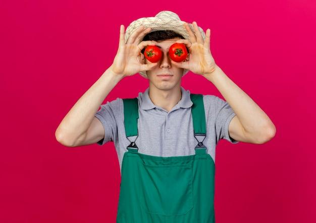 De zekere jonge mannelijke tuinman die tuinierende hoed draagt behandelt ogen met tomaten
