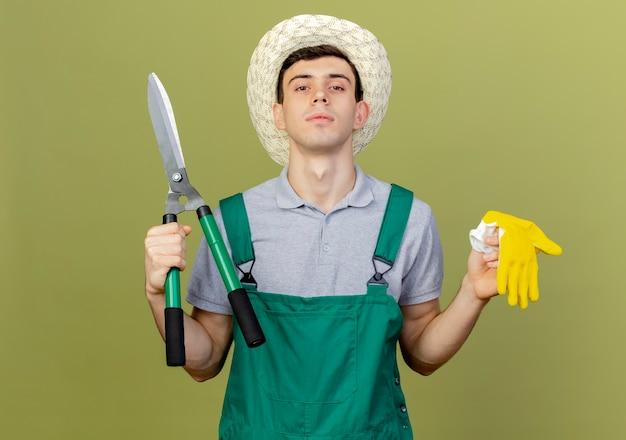 De zekere jonge mannelijke tuinman die tuinierende hoed draagt houdt tondeuse en handschoenen