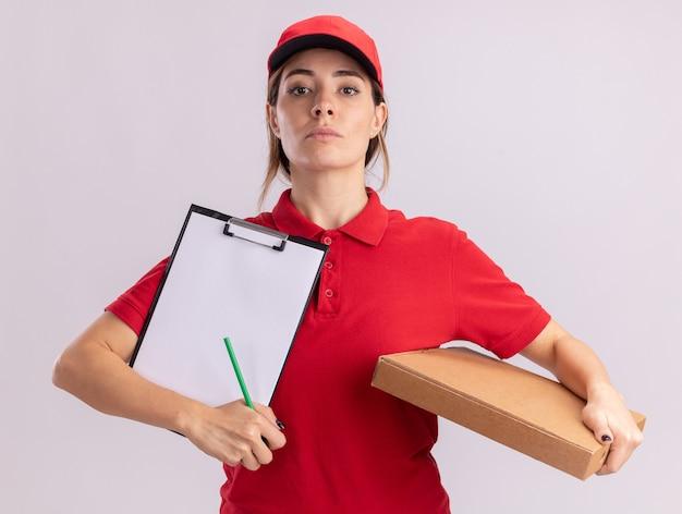 De zekere jonge mooie leveringsvrouw in uniform houdt pizzadoos en klembord dat op witte muur wordt geïsoleerd