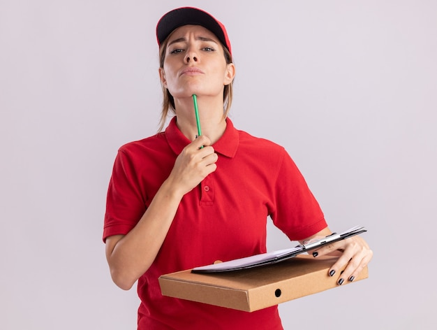 De zekere jonge mooie leveringsvrouw in uniform zet potlood op kin en houdt klembord op pizzadoos die op witte muur wordt geïsoleerd