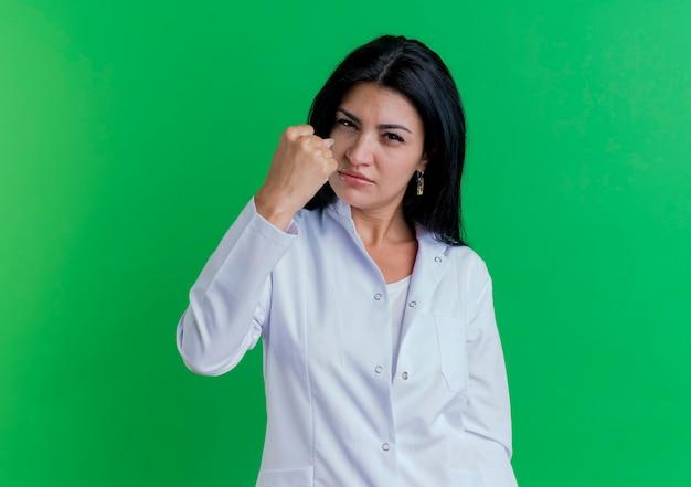 De zekere jonge vrouwelijke arts die medisch kleed draagt, is sterk gebaar dat op groene muur met exemplaarruimte wordt geïsoleerd