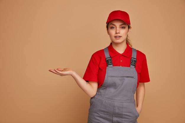 De zekere jonge vrouwelijke bouwvakker die glb draagt en het eenvormige houden dient zak in die lege hand toont