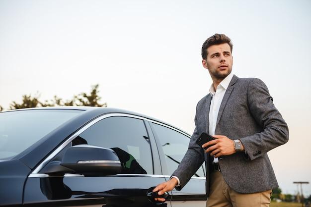De zekere jonge zakenman in kostuum opent zijn auto