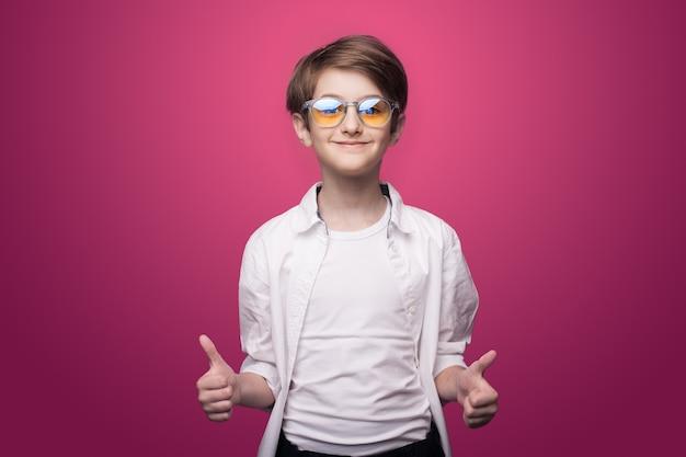 De zekere jongen met bril gebaart het gelijkaardige teken op een rode studiomuur