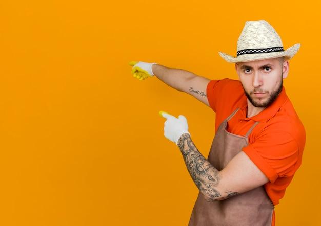 De zekere mannelijke tuinman die het tuinieren hoed en handschoenen draagt wijst op rug met twee handen het kijken
