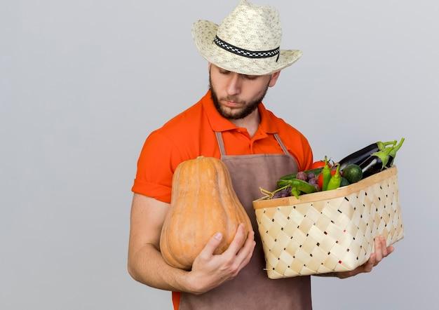 De zekere mannelijke tuinman die tuinierende hoed draagt houdt plantaardige mand en bekijkt pompoen