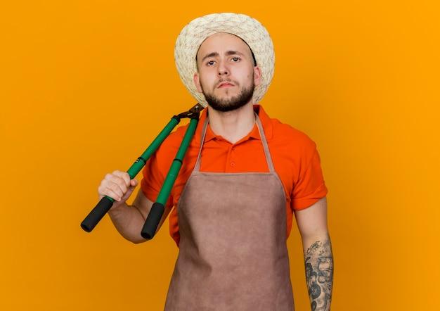 De zekere mannelijke tuinman die tuinierende hoed draagt houdt tondeuse op schouder die op oranje achtergrond met exemplaarruimte wordt geïsoleerd