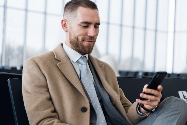 De zekere mensenbaas in luxekostuum controleert e-mail via cellphone alvorens personeel te ontmoeten