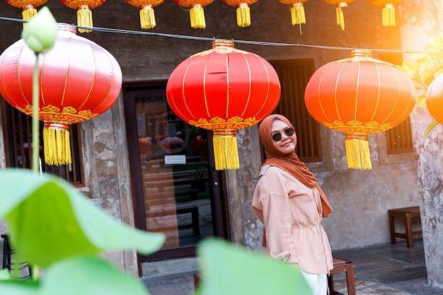 De zekere moslimvrouwentoerist bekijkt de chinese traditionele lantaarn die bij openlucht in de avond hangen, reisconcept. chinees thema.