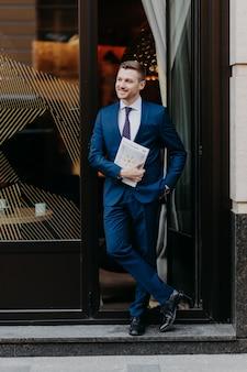 De zekere succesvolle zakenman in formeel kostuum, houdt zak in, houdt tijdschrift