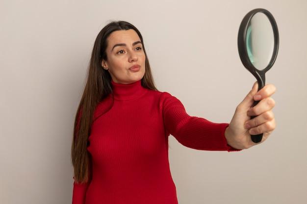 De zekere vrij kaukasische vrouw houdt en bekijkt geïsoleerd vergrootglas