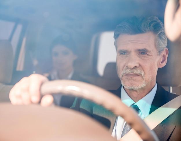 De zekere zakenman in kostuum drijft zijn luxueuze auto.
