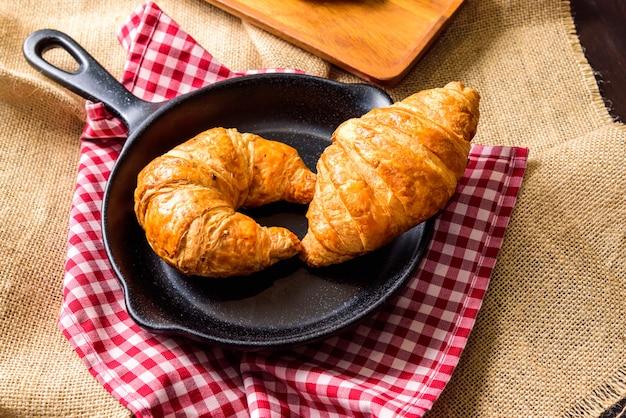 De zelfgemaakte croissant wordt op een zwarte plaat in de vorm van een pan geplaatst.