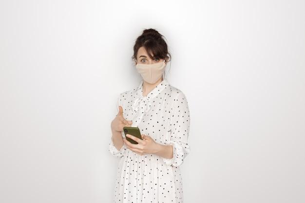 De zelfverzekerde blanke vrouw die een jurk en een medisch masker op het gezicht draagt, wijst naar haar telefoon op een witte studiomuur