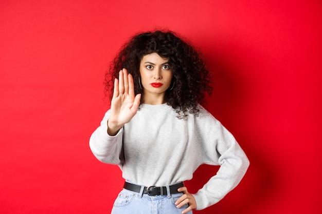 De zelfverzekerde gespannen vrouw steekt haar hand uit om stop te zeggen, keurt actie af en verbiedt het, maakt geen gebaar, staat op een rode achtergrond en verbiedt iets.