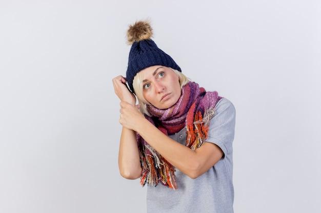 De zelfverzekerde jonge blonde zieke vrouw die de winterhoed en sjaal draagt houdt wapens die kant bekijken die op witte muur wordt geïsoleerd