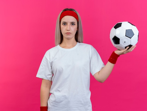 De zelfverzekerde jonge sportieve vrouw met beugels die hoofdband en polsbandjes dragen houdt bal geïsoleerd op roze muur