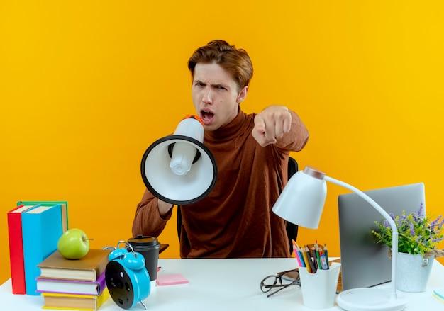 De zelfverzekerde jonge studentenjongen die aan bureau zit met schoolhulpmiddelen spreekt op luidspreker en toont u gebaar